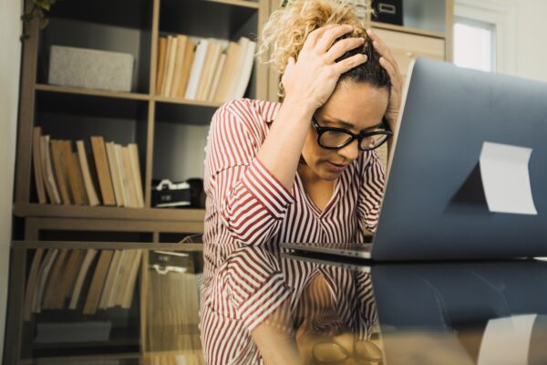 One alone unhappy and sad woman at home in the office using laptop and looking at it